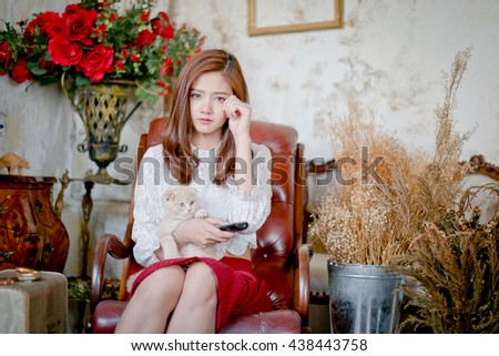 Young girl holding a remote control watching  sad movie on TV.