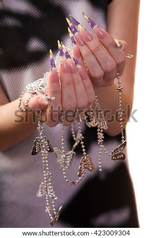 young girl holding a silver chain. Hands with a beautiful design manicure closeup. - stock photo