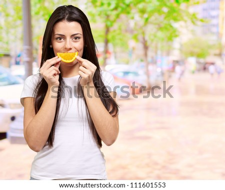 Young Girl Holding A Slice Of Orange, Outdoor