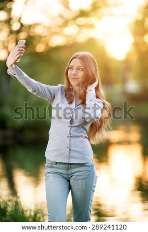 Young girl holding a smartphone digital camera her hands and taking selfie self portrait  herself outdoors enjoying nature  Urban Model woman in Casual jeans in sun light  Backlit Warm Color Tones  - stock photo