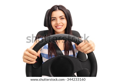 Young girl holding a steering wheel and pretending to drive seated on a car seat isolated on white background - stock photo