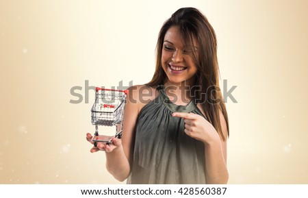 Young girl holding a supermarket cart toy