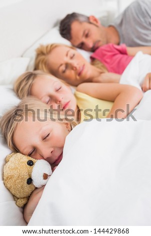 Young girl holding a teddy bear next to her sleeping family in bed - stock photo