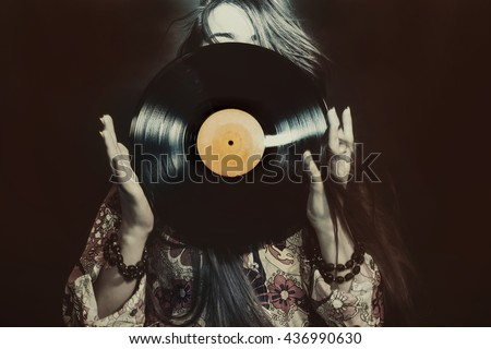 Young girl holding a vinyl record on black background - stock photo