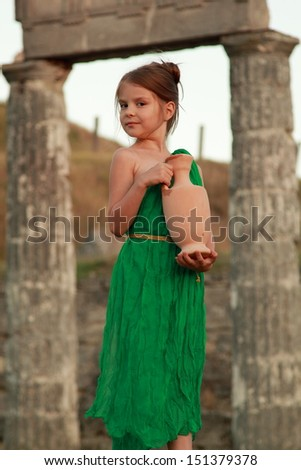Young girl holding an ancient amphora on the excavation of the ancient city Pantikapaion/Girl in a bright emerald green dress standing in the ruins of the ancient city in the role of the Greek goddess - stock photo