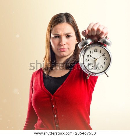 Young Girl holding an antique clock over ocher background