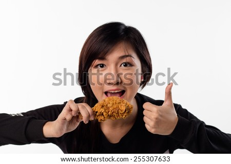 Young girl holding and eating a fried chicken