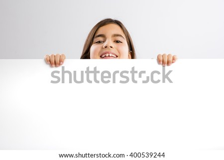 Young girl holding and showing something on a whiteboard - stock photo