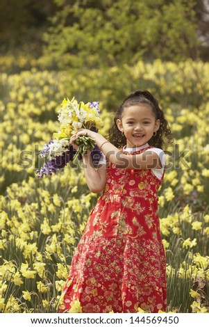 Young girl holding bunch of flowers