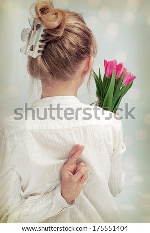 young girl holding bunch of tulips in one hand and second hiding on the back with crossed fingers (vintage style) - stock photo