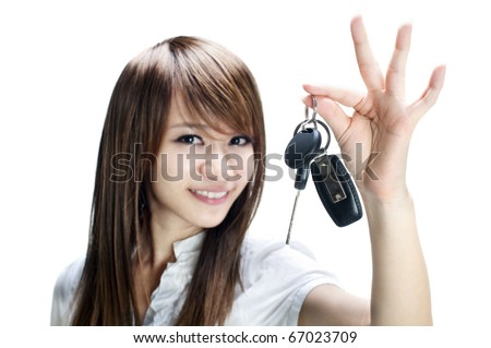 Young girl holding car key on white background - stock photo
