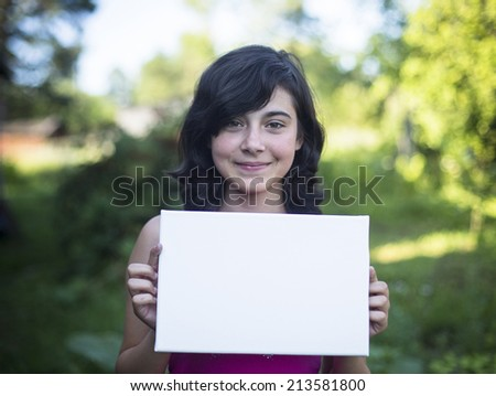 Young girl holding clean white sheet paper, outdoors (for your message) - stock photo