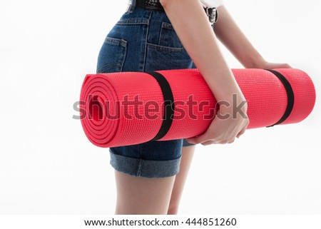 Young girl holding colorful gymnastics mat for fitness in her hands isolated on white background in studio, healthy active lifestyle concept - stock photo