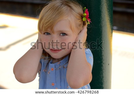young girl holding ears from loud noise - stock photo