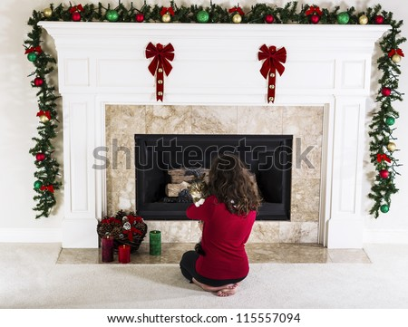Young girl holding family cat in front of holiday decorated natural gas fire place in living room of home - stock photo