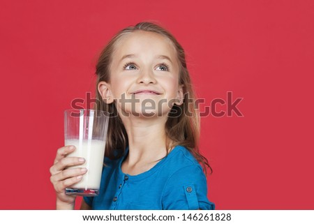 Young girl holding glass of milk while looking up on red background - stock photo