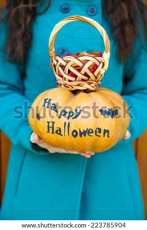 Young girl holding Halloween pumpkin and basket with candies, close-up, outdoors - stock photo