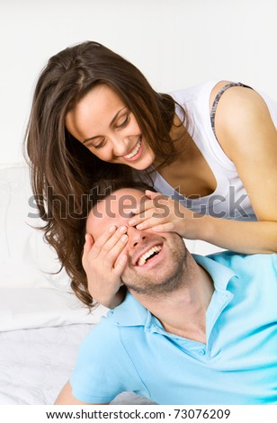 Young girl holding hands on eyes her boyfriend