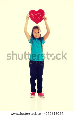 Young girl holding heart pillow - stock photo