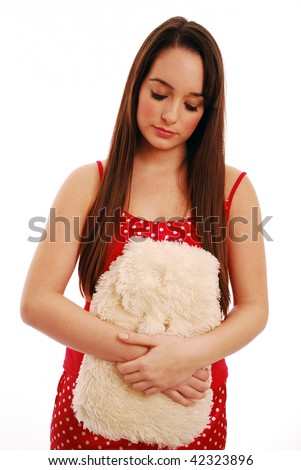 Young girl holding hot water bottle to her tummy - stock photo