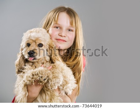 Young girl holding joyful curly spaniel