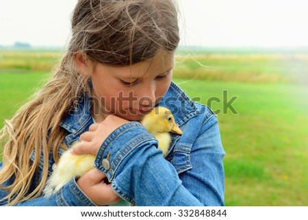 Young girl holding little duck