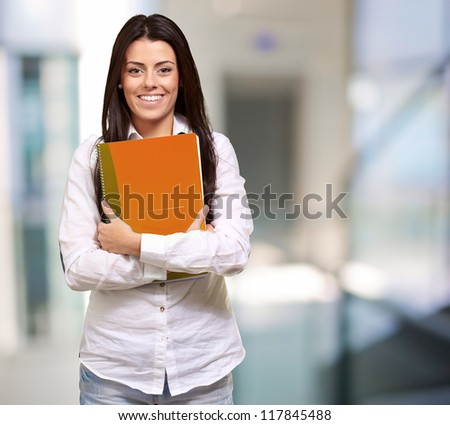 Young girl holding orange book, indoor
