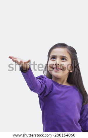 Young girl holding out her hand - stock photo