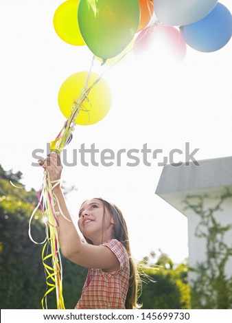 Young girl holding up bunch of balloons over head in lawn - stock photo