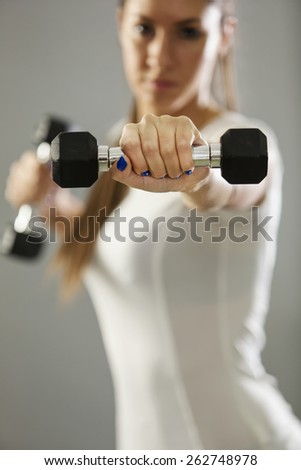 Young girl holding weights - stock photo