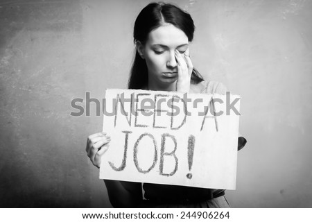 young girl holds a cardboard sign. Need a Job. black and white - stock photo