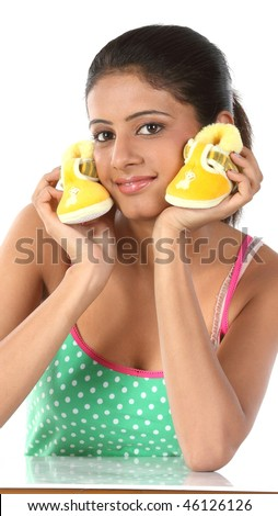 Young girl holds small baby booties in her palm - stock photo