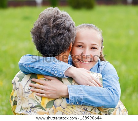 Young girl hug her mother and she enjoying - stock photo