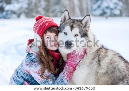 Young girl hugging a dog Husky winter - stock photo