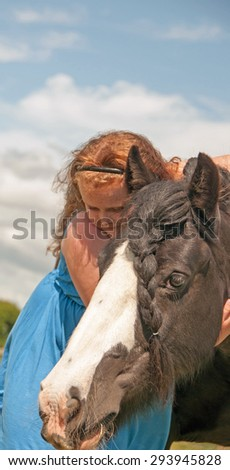 Young girl hugging her pony - stock photo