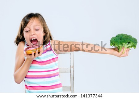 Young girl ignores broccoli and bites into a donut, bad eating choice and unhealthy diet - stock photo