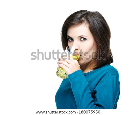 Young  girl in a blue shirt. Drinking orange juice. Isolated on white background - stock photo
