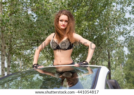 Young girl in a bra with spikes is in the car