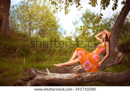 young girl in a bright orange dress and hat sitting on a tree in the fairy summer forest