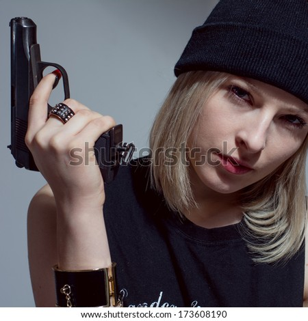 Young girl in a dark cap with a gun in his hand. Blonde with arms - stock photo