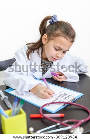 Young girl in a doctor white coat sitting at the table and writing on paper - stock photo