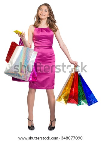 Young girl in a dress holding colorful bags and mobile phone in his hands. - stock photo