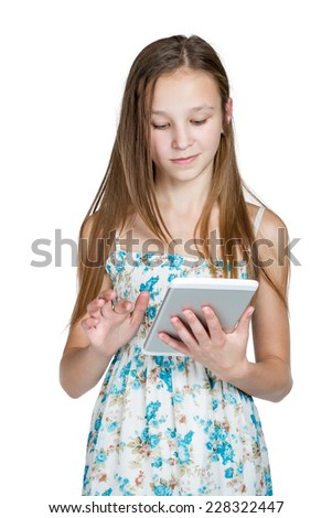 Young girl in a dress works on the tablet standing isolated on white background
