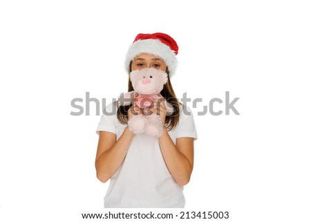 Young girl in a festive red Santa hat with a fluffy pink teddy bear held up in front of her face, isolated on white