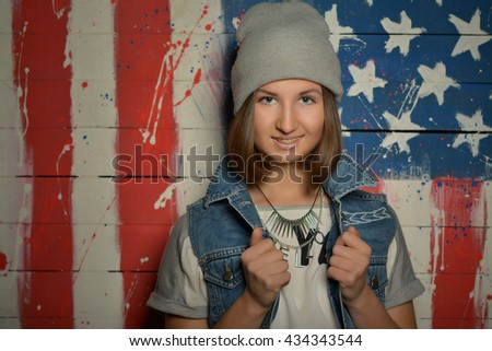 young girl in a gray cap and a denim vest on a background of the American flag - stock photo