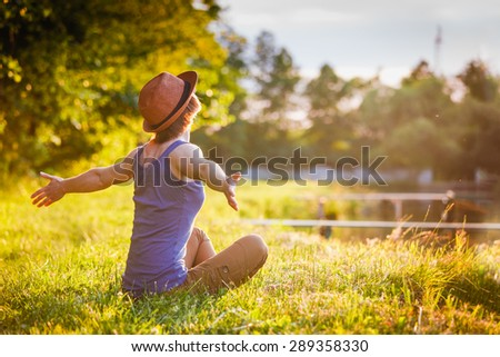 Young girl in a hat Enjoying Nature at sunset - stock photo