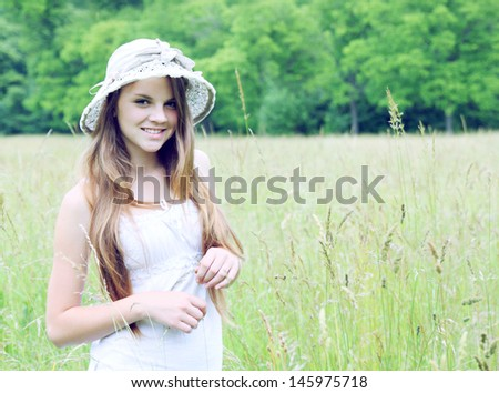 Young girl in a hat walking on the field