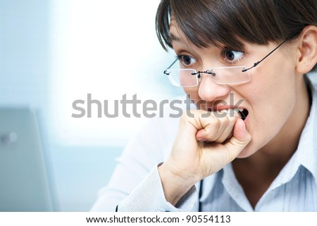 young girl in a horror bite his fist in front of the monitor - stock photo