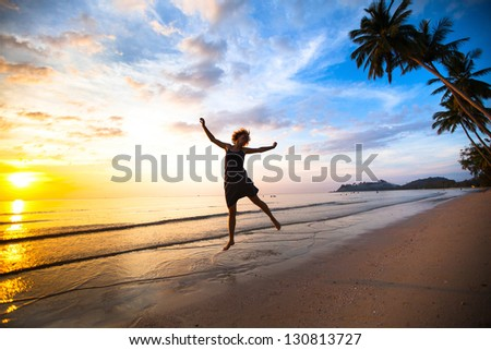 Young girl in a jump on the sea beach at sunset.