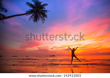 Young girl in a jump on the sea beach at sunset (concept of long-awaited vacation)